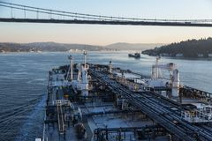 Oil tanker is proceeding through under the bridge in the morning. Big oil tanker is proceeding through under the bridge in the morning Stock Photo
