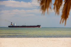 Oil Tanker Sailing Past Tropical Beach and Palm Tree Royalty Free Stock Photography