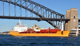Oil Tanker Sailing Under The Sydney Harbour Bridge. Giant oil tanker ship sailing under the famous Sydney Harbour Bridge on a beautiful winter's day in Australia Royalty Free Stock Images