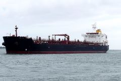 Oil Tanker ship in harbor. Tanker ship transporting petroleum products in the fairway proceeding to the Oil Terminal of Lorient, France. Horizontal side view Royalty Free Stock Image