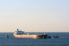 Oil tanker ship at sea with three tug boats. Large oil tanker ship at sea, accompanied by three tug boats Royalty Free Stock Photo