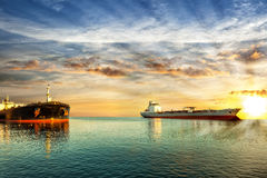 Oil tanker ships riding at anchor. Two tanker ships on sea in the rays of the setting sun Royalty Free Stock Images