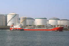 Oil Tanker and Silos. Red oil tanker among oil storage tanks in Rotterdam harbor Stock Photography