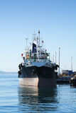 Oil-tanker. Small Oil-tanker unloading its cargo at an oil terminal Stock Photos