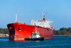 Oil tanker and a tugboat. A huge red oil tanker and a tugboat at work Stock Images