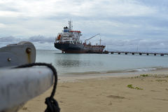 Oil tanker vessel at dock with boat bow in foreground  anchor pu Royalty Free Stock Photography