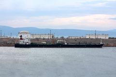 Oil tanker waiting to be unloaded in small harbor Royalty Free Stock Photography