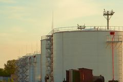 Oil tanks. Row of the big white oil tanks at sunset Stock Photography