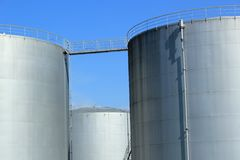 Oil tanks. Big grey oil tanks and blue sky Royalty Free Stock Photo