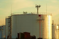 Oil tanks at sunset. Row of the big white oil tanks at sunset Royalty Free Stock Images