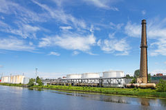 Oil terminal near river in sunny day Royalty Free Stock Photo