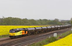 Oil train in a deluge. HARROWDEN, UK - MAY 6: A Colas Rail operated class 60 diesel locomotive hauls a rake of empty oil tankers back to the coastal fuel Stock Photos