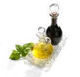 Oil and vinegar. Two glasses oil and balsamic vinegar on glass plate Royalty Free Stock Photography