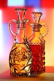 Oil & Vinegar. Bottles of olive oil and red wine vinegar against colorful abstract background Royalty Free Stock Images