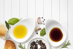 Oil and Vinegar Food Background. With fresh bread, peppercorns and herbs over white wood panel Stock Images
