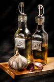 Oil, Vinegar and Garlic. Oil Vinegar and Garlic on black background Stock Photos