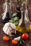 Oil and vinegar, gralic, tomatoes with herb Royalty Free Stock Photography
