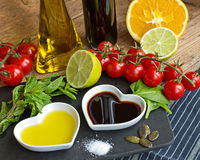 Oil and vinegar in heart shaped bowls displayed with fresh produ Royalty Free Stock Image