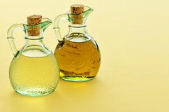 Oil and Vinegar. Olive oil and rice wine vinegar in pretty glass jugs on a warm yellow background with room for text stock image