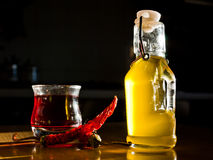 Oil, vinegar, pepper. A bottle of olive oil, a cup of red vinegar, and two chili peppers Royalty Free Stock Photo