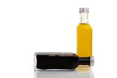 Oil and vinegar set. Vinegar bottle lays in front of an oil bottle Royalty Free Stock Photo