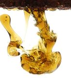 Oil in Water. Dark brown and golden oil pouring into clear water Stock Photos