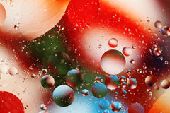 Oil and Water Background. Oil floating on water over bright colors Royalty Free Stock Image