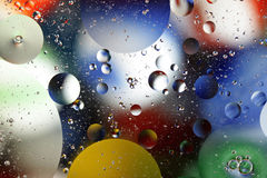 Oil and Water Background III. Oil floating on water over bright colors Stock Photography