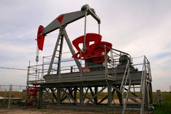 Oil well. Grey oil pump on a green field Stock Image