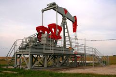 Oil well. Grey oil jack on a green field Royalty Free Stock Photo