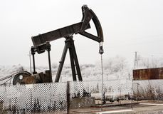Oil well. Old rusty oil well on a winter land Royalty Free Stock Photo