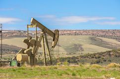 Oil Well Against Mountains and Blue Cloudy Sky Spring Scene. In Colorado royalty free stock photo