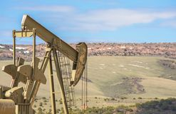 Oil Well Against Mountains and Blue Cloudy Sky Spring Scene. In Colorado stock image