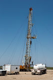 Oil Well Drilling Rig. Oil drilling crew, called roughnecks, work a derrick rig in the oil well fields Stock Photo
