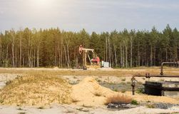 Oil well for the extraction of oil and gasoline and gas on the background of the forest, the production of fuel-combustible stock image