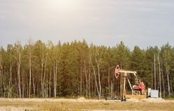 Oil well for the extraction of oil and gasoline and gas on the background of the forest, the production of fuel-combustible royalty free stock photography