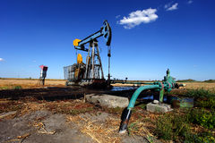 Oil well in the field. Oil well with a part of the pipeline and spilled oil in the field in Serbia stock images