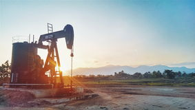 OIL well. Machine on sunset stock photography
