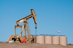 Oil Well Pump. Jack with storage barrels in oil fields of North Dakota. Blue sky. Horizontal. Copy space stock photo