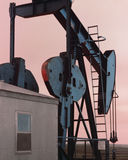 OIL WELL PUMP JACK AT SUNSET Royalty Free Stock Photography