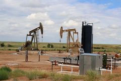 Oil Well Pump Jack drilling site. Two oil - gas well pump jack at drilling site with equipment and holding tanks on praries with low hill behind and blue cloudy stock photos