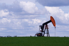 Oil well pump jack in green field royalty free stock image