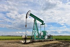 Oil Well Pump Jack. An image of a working oil well pump jack on a cloudy day stock photography