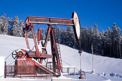 Oil well pump jack mountains Royalty Free Stock Photos
