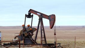 Oil Well Pump Jack pumping crude oil for fossil fuel energy. American Petroleum Oil and Gas Industry equipment extracting from a