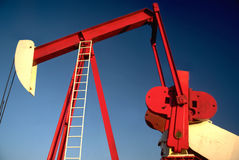 OIL WELL. Red Oil Well Pump Jack Against Blue Background. American oil gas industry. Oil pump royalty free stock image