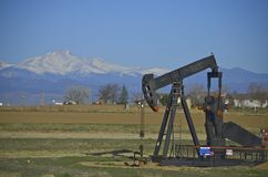 Oil well, pump jack with snow capped mountains royalty free stock image