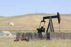 Oil well pump with wind generators. In the background, showing old and new technology, or renewable and non renewable resources in northern California royalty free stock photography