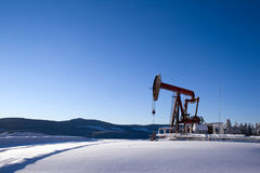 Oil well pumpjack mountain snow Stock Image