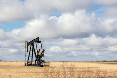 Oil well. Sitting in a golden field on a warm fall day with clouds in the sky royalty free stock photography